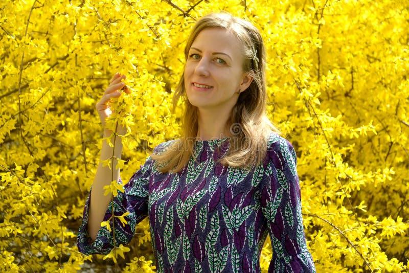 La mujer joven feliz contra la perspectiva de la floración forsythia Retrato foto de archivo libre de regalías