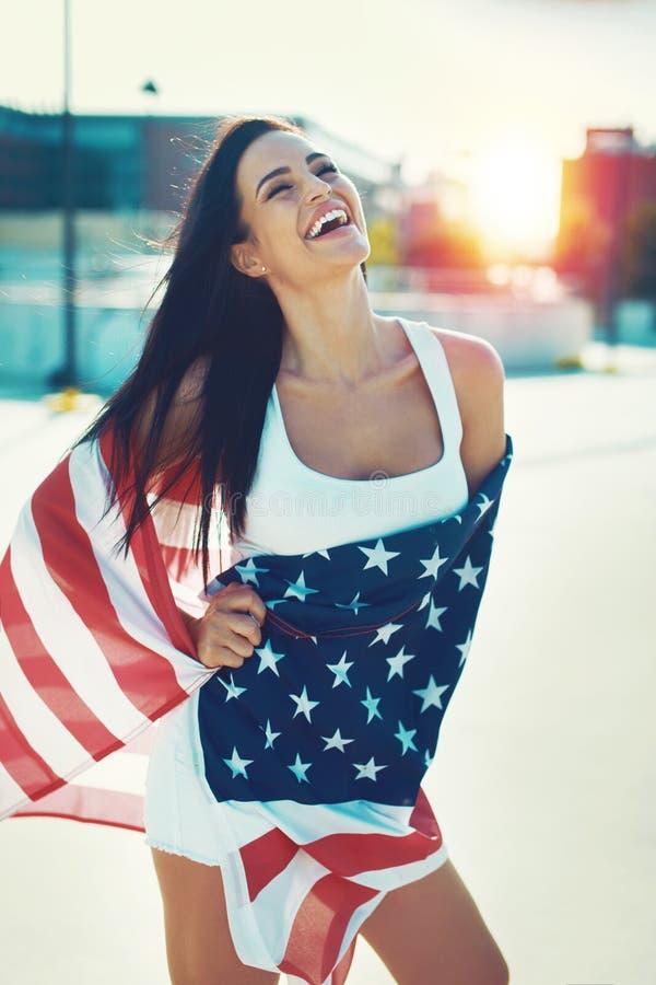 La mujer joven feliz cubierta con los E.E.U.U. señala la risa por medio de una bandera al aire libre imagen de archivo libre de regalías