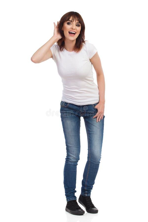 La mujer joven feliz curiosa está escuchando detras de las puertas imagen de archivo
