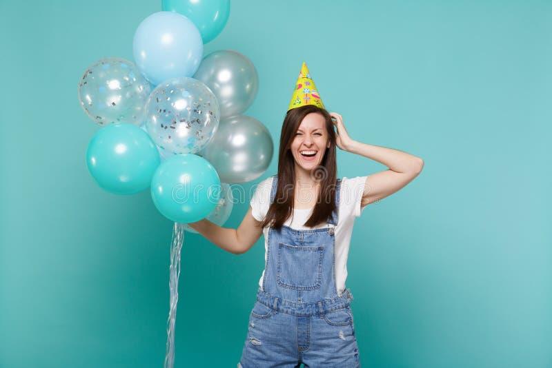 La mujer joven feliz de risa en el sombrero del cumpleaños que ponía la mano en la cabeza y la celebración, celebrando los balone foto de archivo