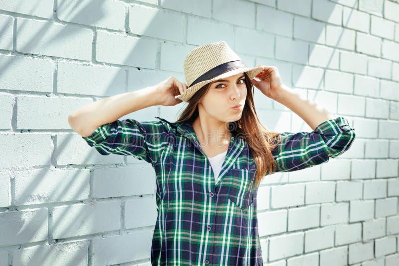 La mujer joven feliz en camisa de tela escocesa hace caras, cerca de la pared de ladrillo azul foto de archivo libre de regalías