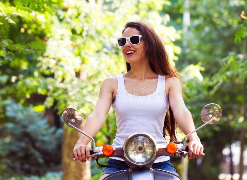 La mujer joven feliz en la vespa en parque de la ciudad en el verano imagen de archivo libre de regalías
