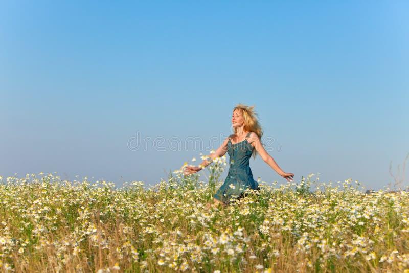 La mujer joven feliz en los tejanos los sundress salta en el campo de camomiles en un día soleado imagen de archivo