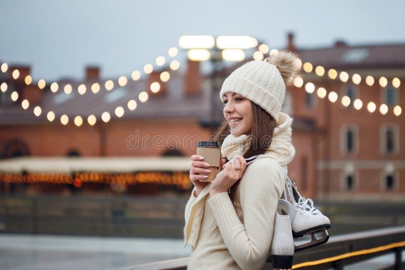 La mujer joven feliz en suéter y sombrero hechos punto es patinaje que va imagen de archivo