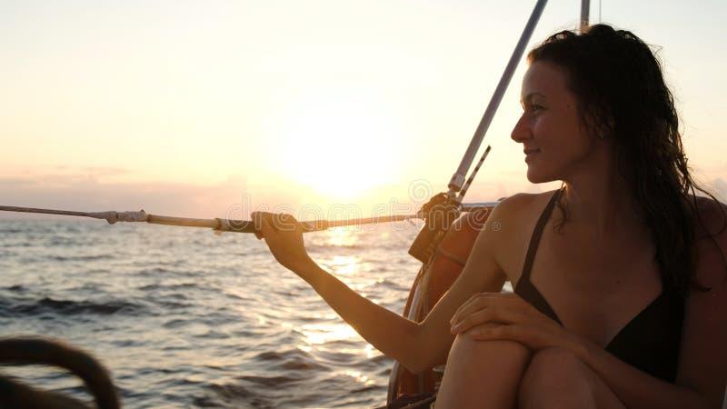La mujer joven feliz en un traje de baño se sienta en detrás de un yate navegante en la puesta del sol imagen de archivo