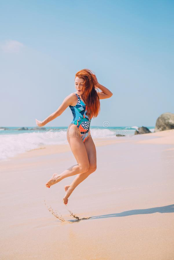 La mujer joven feliz está saltando en la playa imágenes de archivo libres de regalías