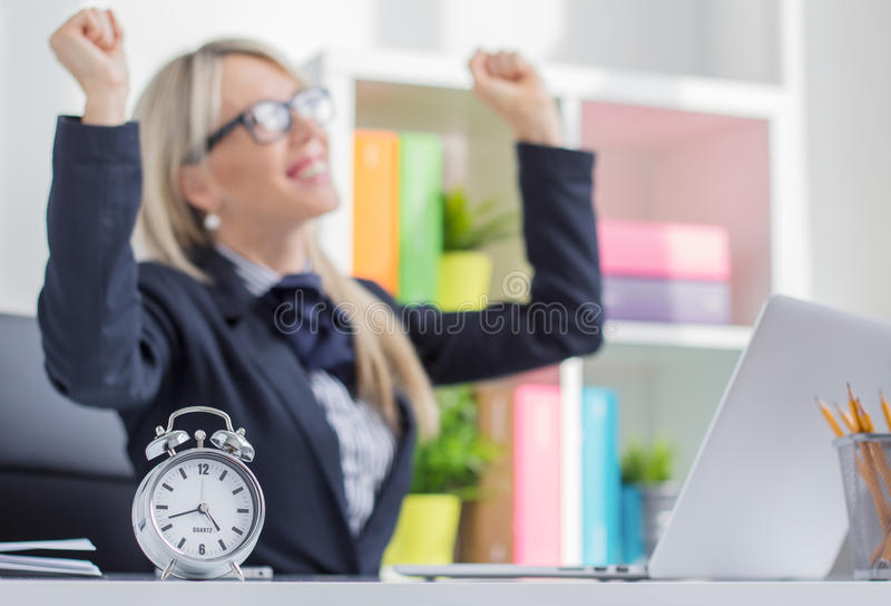 La mujer joven feliz goza el acabar de trabajo el tiempo imagen de archivo