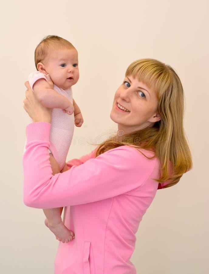 La mujer joven feliz levanta en las manos del bebé imagen de archivo