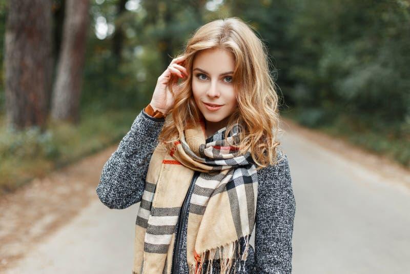 La mujer joven feliz linda en una capa elegante de la primavera en una bufanda a cuadros del vintage camina en el parque en un dí foto de archivo