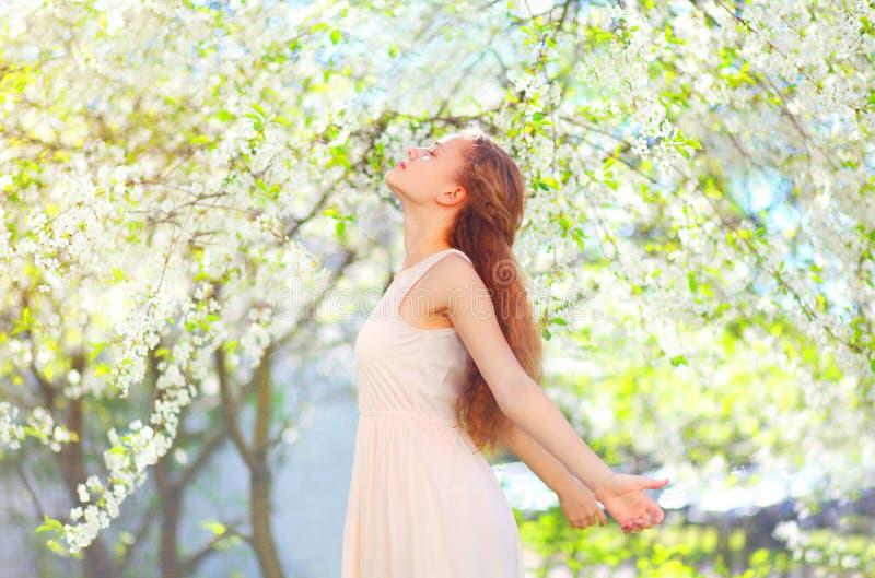 La mujer joven feliz que goza del olor florece sobre jardín de la primavera foto de archivo libre de regalías