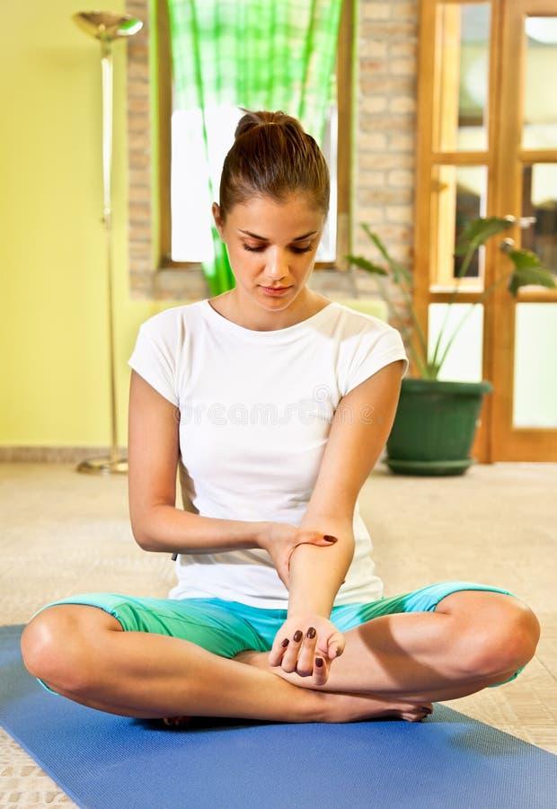 La mujer joven feliz que hace a uno mismo del brazo da masajes en casa. foto de archivo libre de regalías