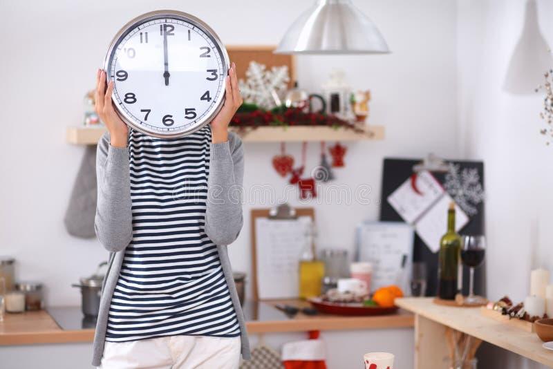 La mujer joven feliz que mostraba el reloj en la Navidad adornó la cocina imágenes de archivo libres de regalías