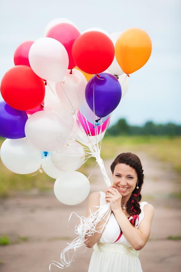 La mujer joven feliz que se sostiene en globos coloridos del látex de las manos aventaja foto de archivo