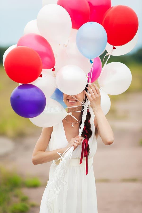 La mujer joven feliz que se sostiene en globos coloridos del látex de las manos aventaja imagen de archivo libre de regalías