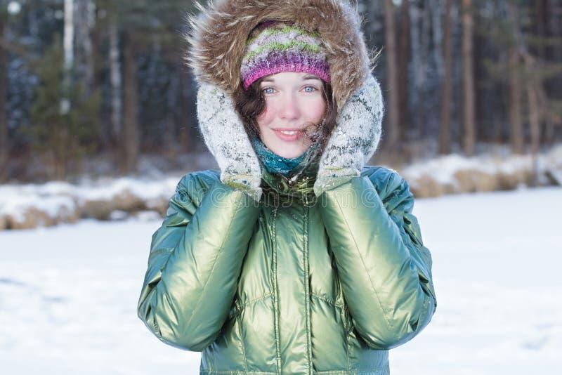 La mujer joven feliz que sostiene las manoplas lanosas acerca a su cabeza en bosque del invierno al aire libre imagenes de archivo