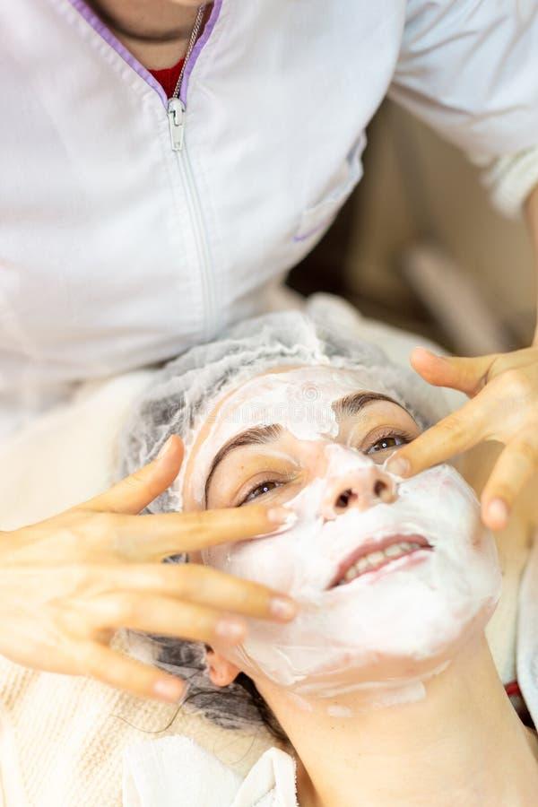 La mujer joven feliz recibe un tratamiento facial en centro del balneario imagenes de archivo