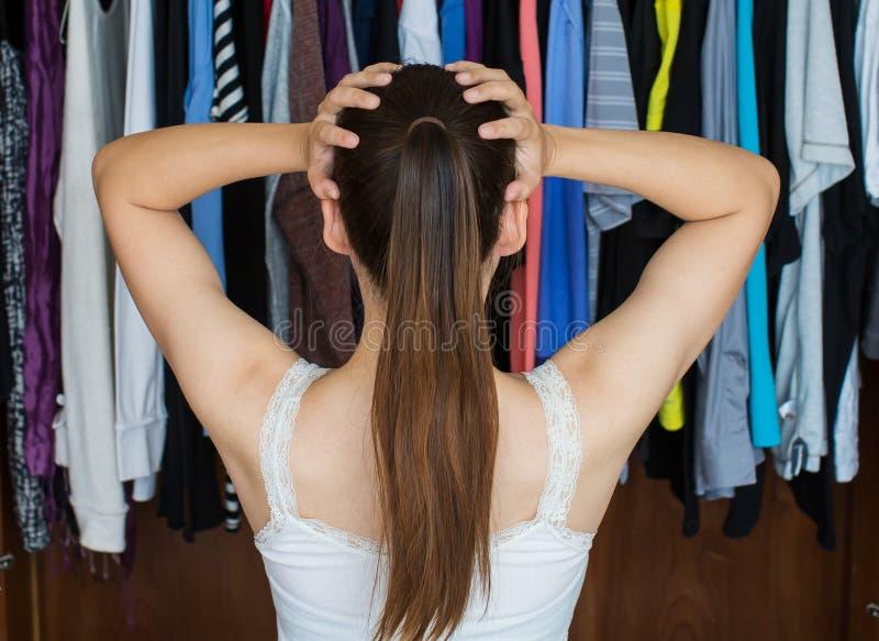 La mujer joven frustrada no puede decidir qué llevar de ella cerca fotos de archivo