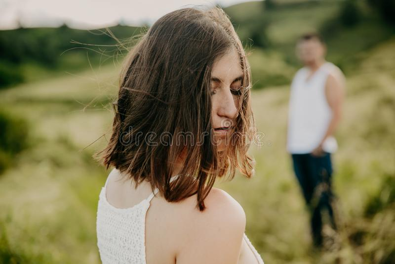 La mujer joven frustrada que mira en distancia, piensa en las relaciones, sentándose por separado con el hombre fotografía de archivo libre de regalías