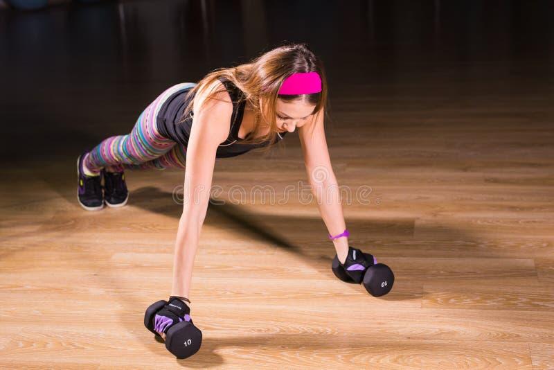 La mujer joven fuerte que hace pectorales ejercita con pesas de gimnasia Modelo de la aptitud que hace el entrenamiento intenso e foto de archivo