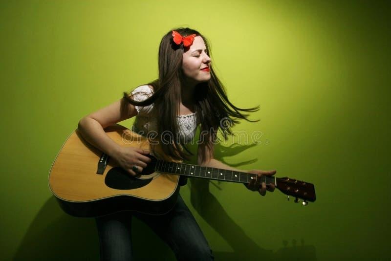 La mujer joven goza el tocar de la guitarra imagen de archivo