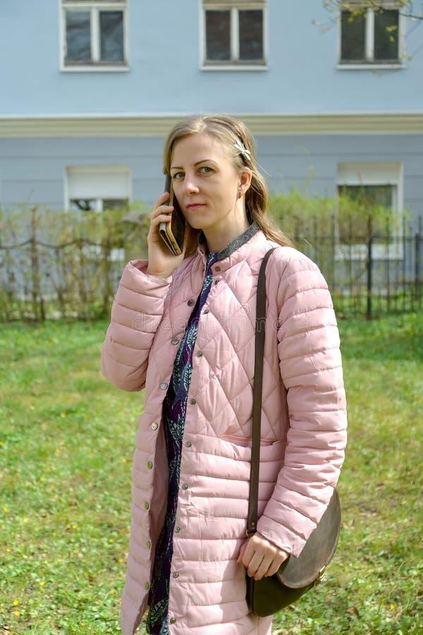La mujer joven habla por el teléfono móvil, colocándose en la calle imagen de archivo libre de regalías