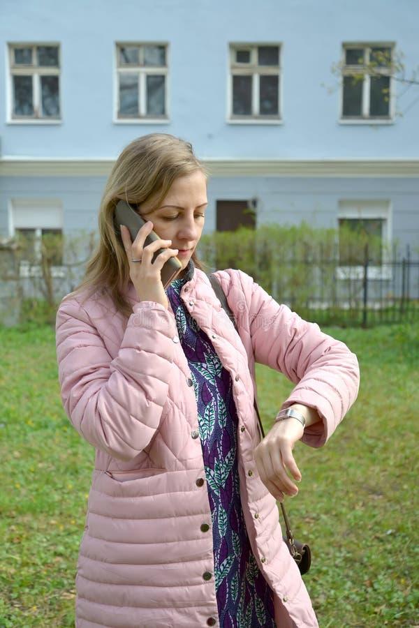 La mujer joven habla por el teléfono móvil y las miradas en el reloj imagen de archivo