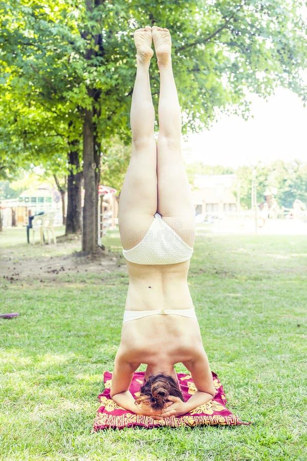 La mujer joven hace posiciones del pino en un parque fotos de archivo