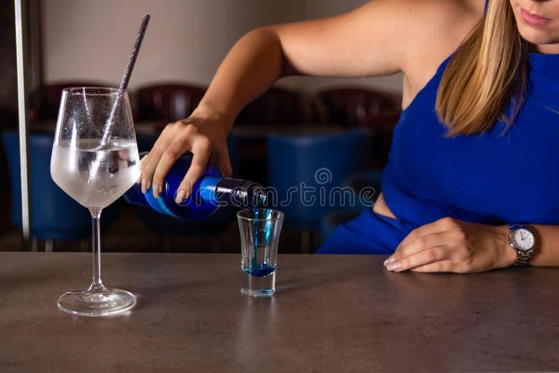 La mujer joven hace un cóctel azul de la laguna en la barra en el restaurante imagen de archivo