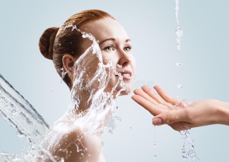 La mujer joven hermosa adentro salpica del agua clara imagen de archivo