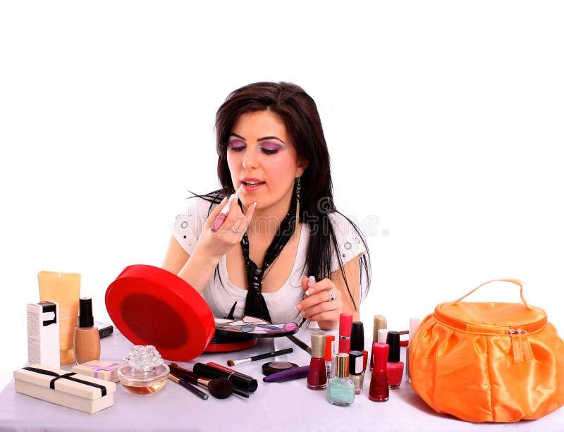 La mujer joven hermosa aplica su lustre del labio imagen de archivo