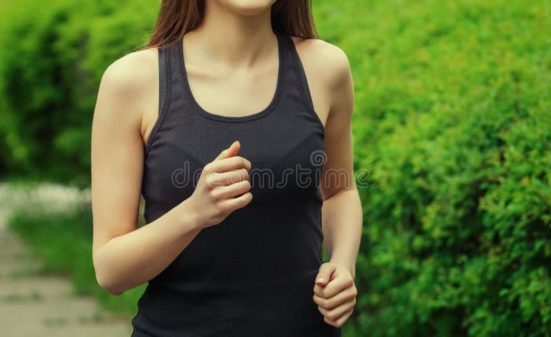 La mujer joven, hermosa, atlética por la mañana corre en el parque fotografía de archivo