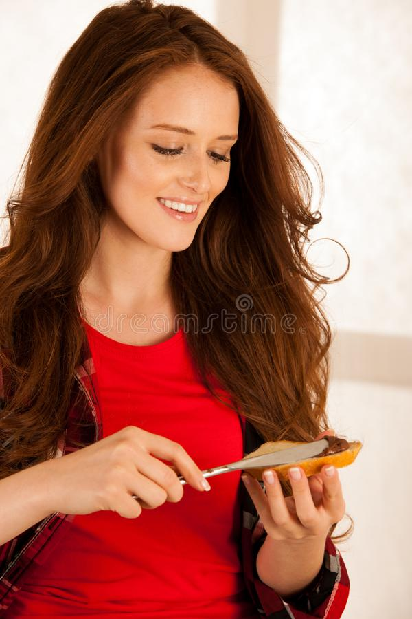 La mujer joven hermosa atractiva come el pan y el nugat se separó para imagen de archivo libre de regalías