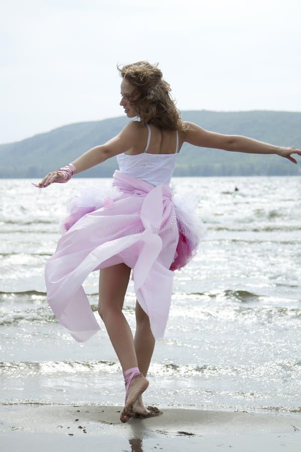 La mujer joven hermosa baila en una playa fotografía de archivo
