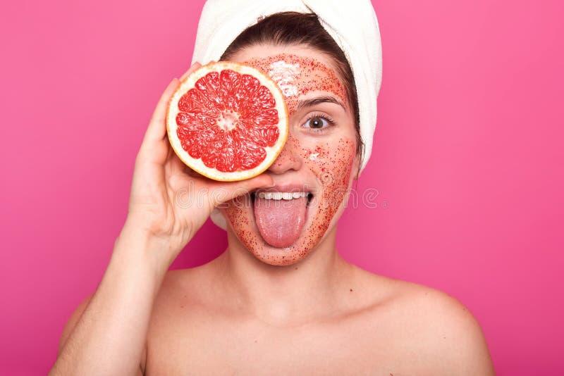 La mujer joven hermosa con brillante friega en su cara lleva a cabo la mitad del pomelo de la violaci?n en una mano, se pega haci imagenes de archivo