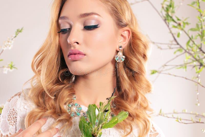 La mujer joven hermosa con el pelo rizado rubio, lleva la ropa y la joya elegantes, fotos de archivo
