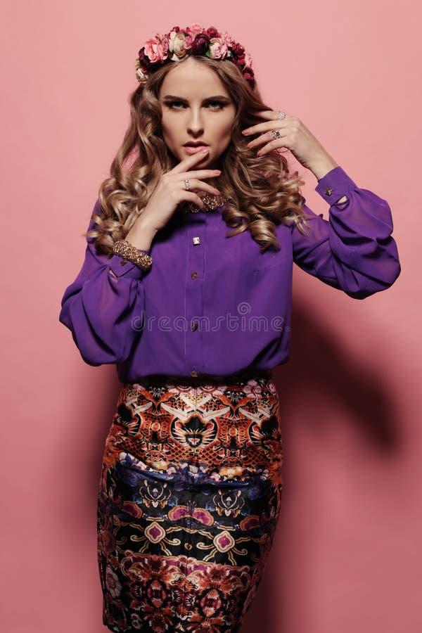La mujer joven hermosa con el pelo rizado rubio, lleva la ropa y la joya elegantes, imagen de archivo