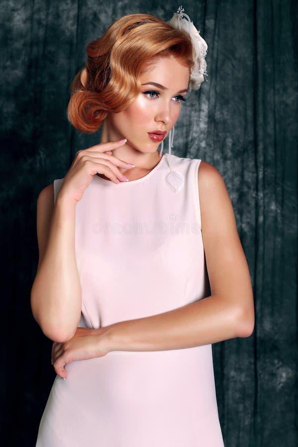 La mujer joven hermosa con el pelo rojo corto en estilo retro, lleva el vestido blanco elegante foto de archivo libre de regalías