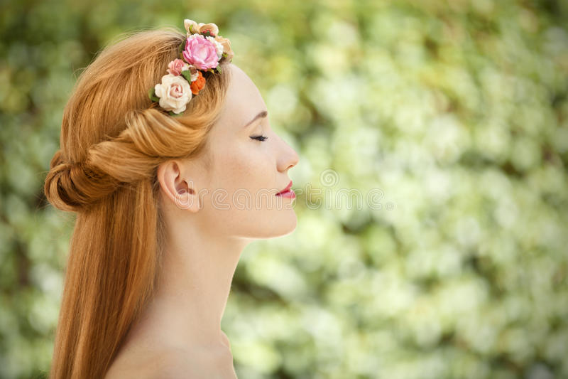 La mujer joven hermosa con las flores enrruella en pelo foto de archivo