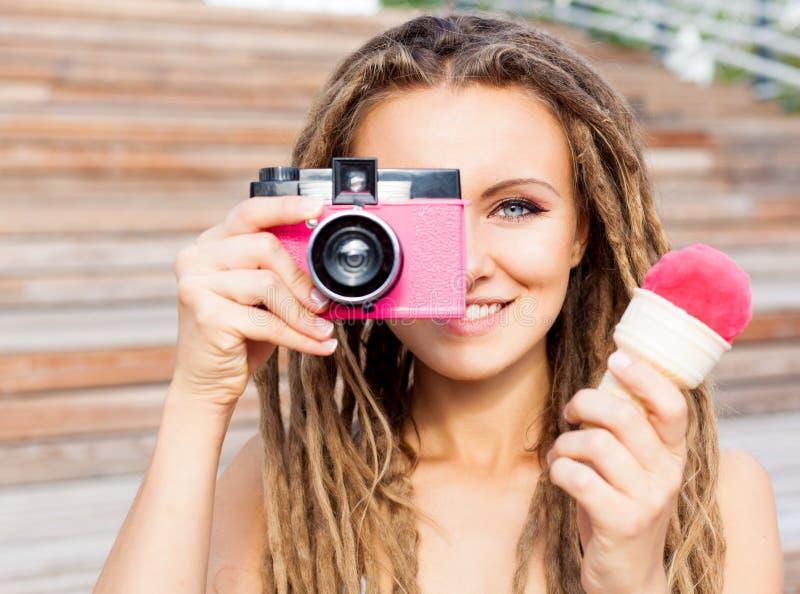 La mujer joven hermosa con los dreadlocks que toman las fotos con la cámara retra de la película del rosa del vintage y el helado fotografía de archivo