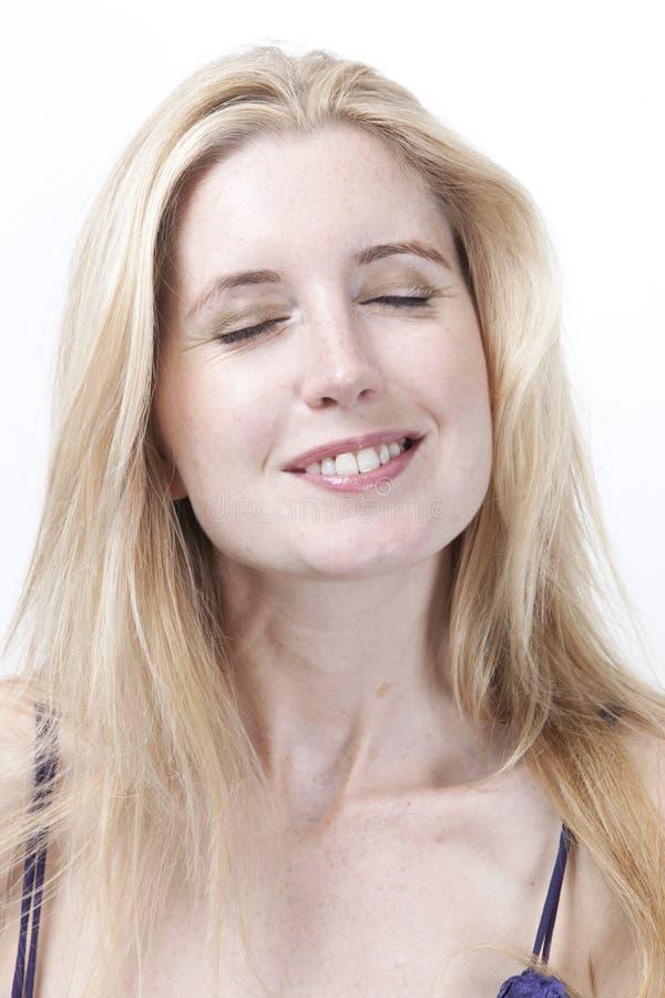 La mujer joven hermosa con los ojos cerró la sonrisa contra el fondo blanco imagen de archivo