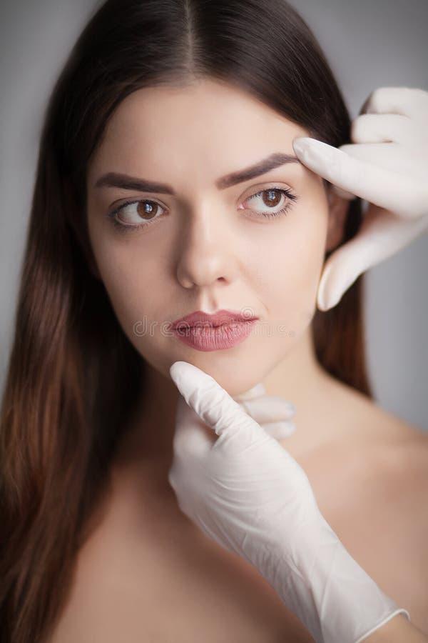 La mujer joven hermosa con tacto fresco limpio de la piel posee la cara Fac fotos de archivo libres de regalías