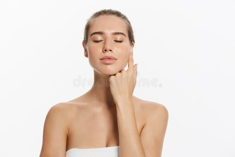 La mujer joven hermosa con tacto fresco limpio de la piel posee la cara Tratamiento facial Cosmetología, belleza y balneario fotografía de archivo