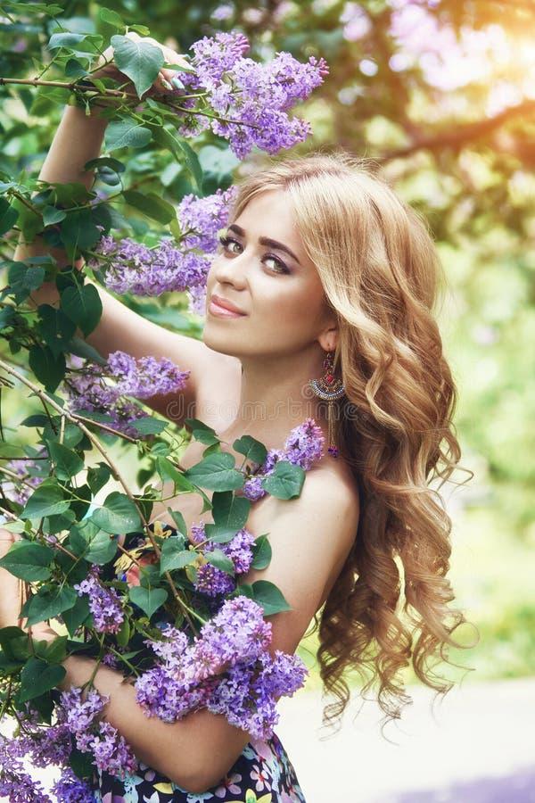 La mujer joven hermosa de la moda al aire libre rodeada por la lila florece verano Arbusto de lila del flor de la primavera Retra imagen de archivo libre de regalías