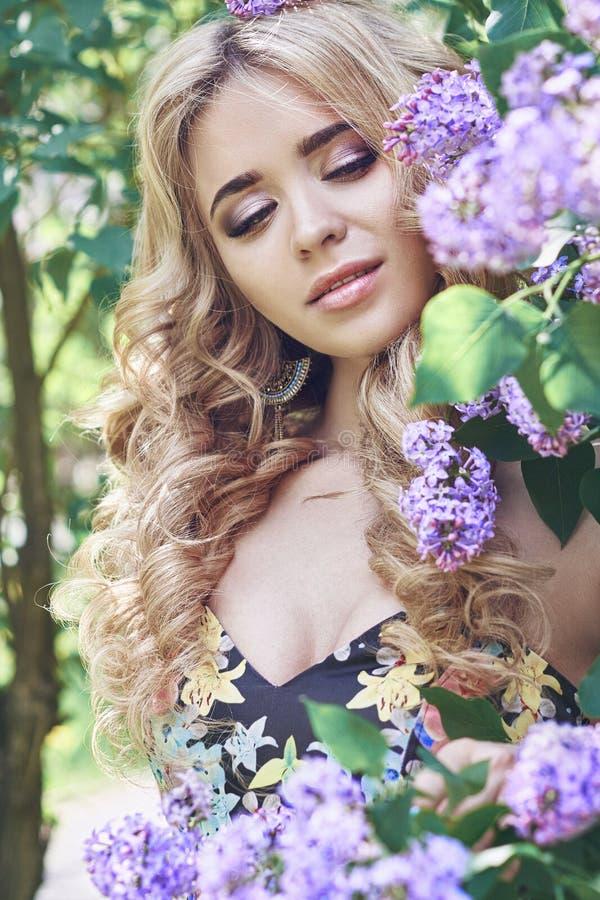 La mujer joven hermosa de la moda al aire libre rodeada por la lila florece verano Arbusto de lila del flor de la primavera Retra imágenes de archivo libres de regalías