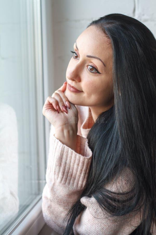 La mujer joven hermosa del primer con la sonrisa larga del pelo negro mira hacia fuera la ventana, reflejada en la ventana foto de archivo libre de regalías