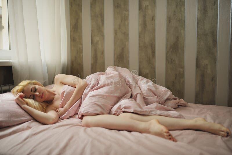 La mujer joven hermosa duerme en el dormitorio foto de archivo