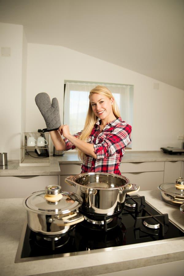 La mujer joven hermosa en cocina cocina una comida deliciosa imagenes de archivo