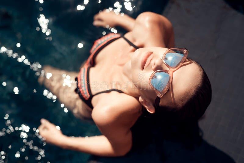 La mujer joven hermosa en gafas de sol se está enfriando hacia fuera en piscina en el tiempo de verano foto de archivo