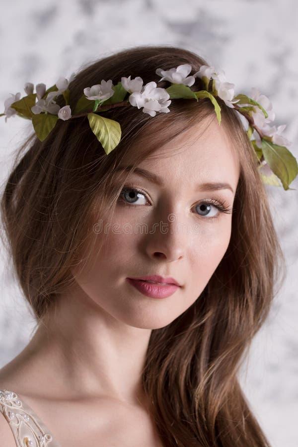 La mujer joven hermosa en guirnalda con el pelo largo presenta imagen de archivo