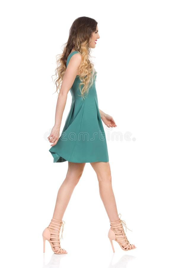La mujer joven hermosa en Mini Dress And High Heels verde está caminando Vista lateral imagen de archivo